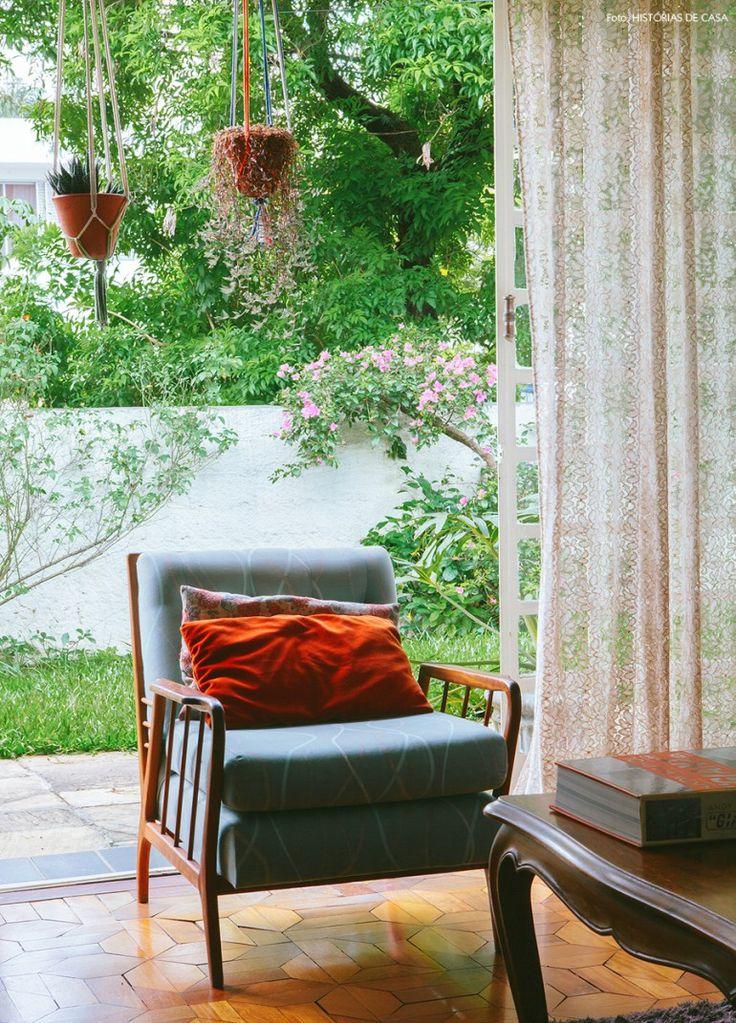 Sala de estar de uma casa antiguinha com poltrona vintage e jardim ao fundo.