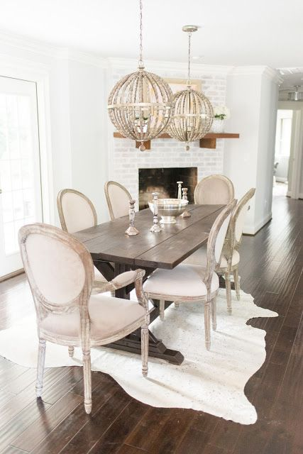 The Before of this space is unreal. Dining room with painted brick fireplace, over sized wood bead chandeliers, hand made farm table, metallic cow hide rug