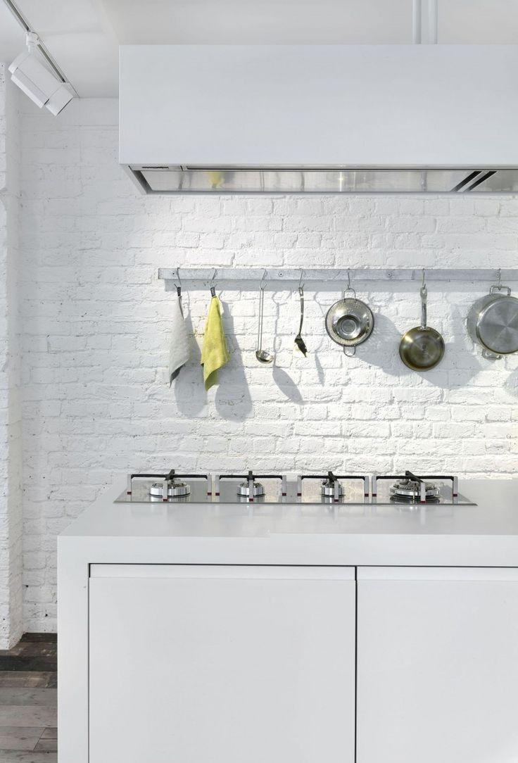 Moderne witte keuken met witte achterwand.