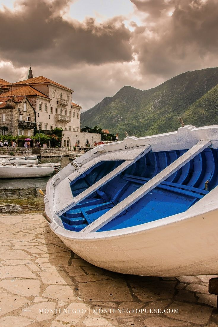 A classic Montenegrin 'barka' (boat) sits outside the stone palaces lining the shore of Perast, Bay of Kotor, Montenegro.