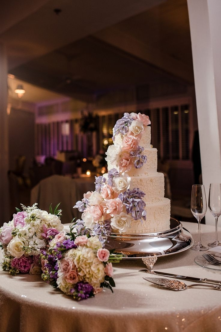 Spring wedding cake with pink and purple floral accents at the Coral Bay Club in Atlantic Beach NC. Cake by Douglass Ann Swanson. Flowers by Designs by Ernest. Photos by Cynthia Rose Photography.