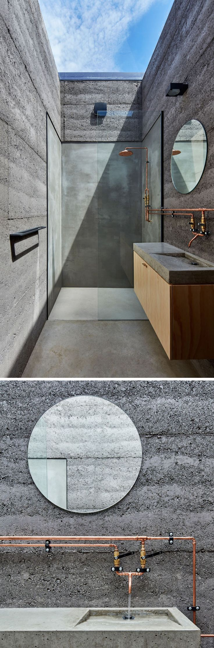 The bathroom has walls made from rammed earth in a charcoal color., and a large skylight makes it appear as though you are showering outdoors.