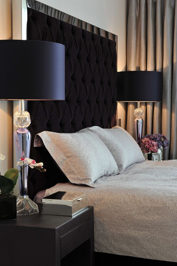Black headboard, lamps and nightstands paired with white linens.