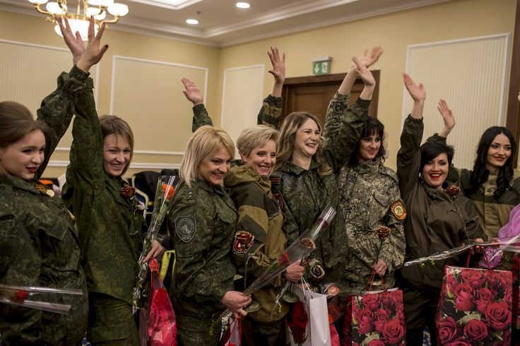 Female soldiers of the self-proclaimed Donetsk People's Republic wave backstage, during a beauty parade to mark International Women's Day in Donetsk on March 7, 2015.