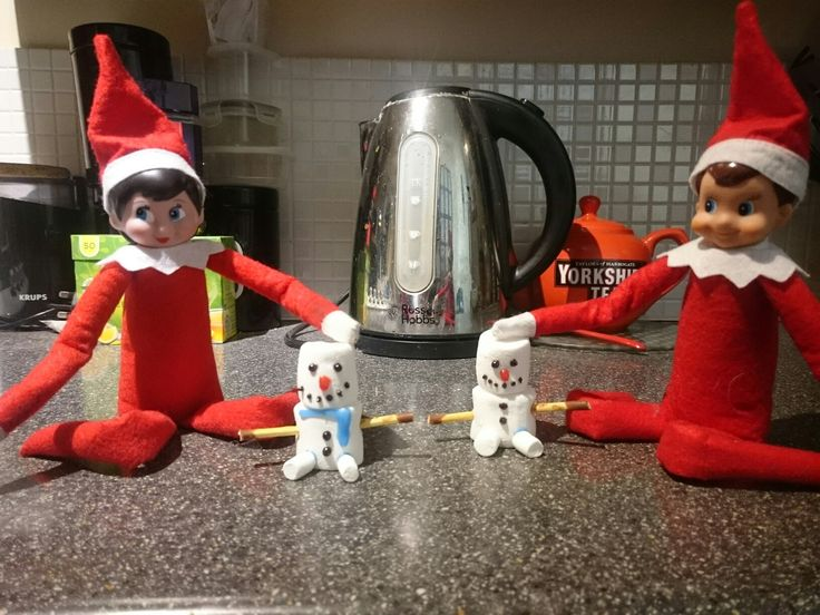 snowmen made from marshmallows with writing icing and mikado sticks for arms
