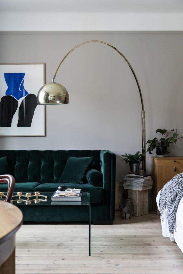 Stue med grøn velour sofa og art deco lampe i messing.