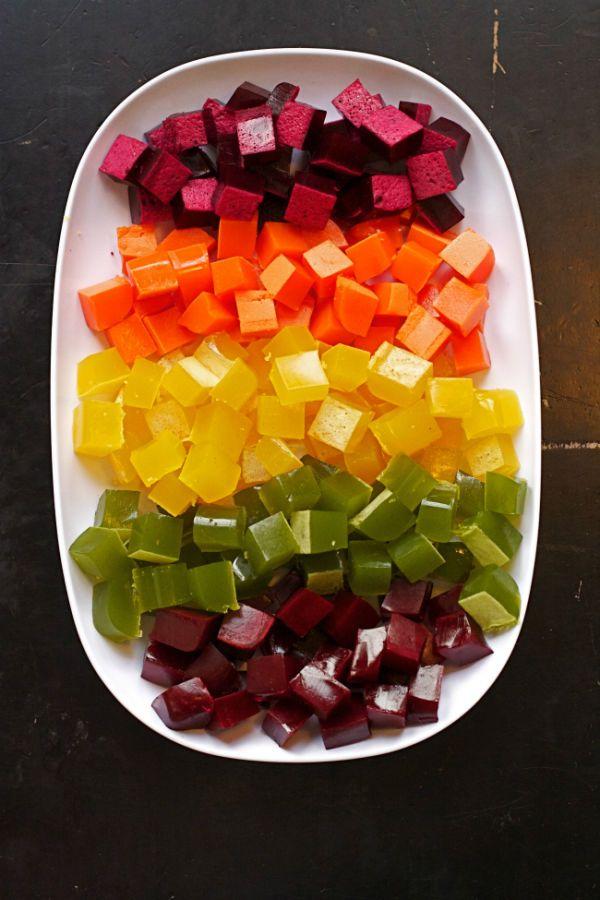 rainbowgummies Rojo/rosado: remolachas, fresas, zanahorias y un poco de jugo de limón.  Anaranjado: zanahorias, naranjas, jengibre y un poco de jugo de mango.  Amarillo: pimentón amarillo, remolacha amarilla, pera amarilla, manzana amarilla y un poco de jugo de limón.  Verde: col crespa, kiwi, pepino, manzana verde y lima. Otra opción es utilizar uvas verdes.  Morado: repollo morado, moras, arándanos, un poco de remolacha y una manzana. También puedes usar uvas concordia.