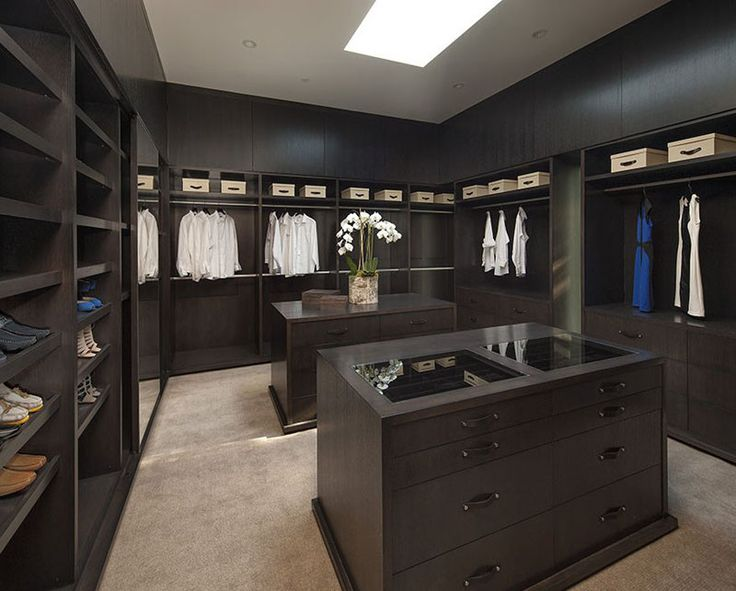 This walk-in closet could be mistaken for a fashion store, with its dark wood and two islands for storing and displaying accessories.