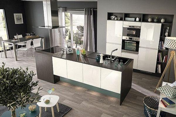 L'îlot central noir et blanc de cette cuisine délimite les fourneaux du reste de la pièce. Un aménagement de cuisine ouverte moderne à souhait.