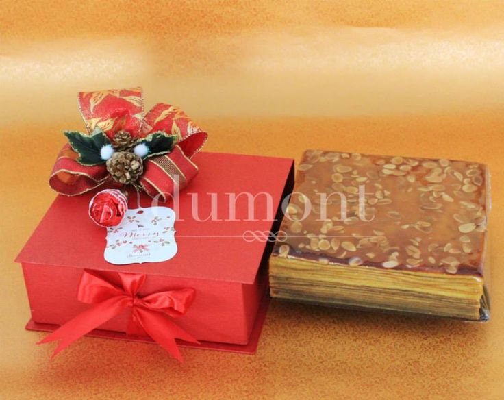 Rich layered cake in a red hardbox with christmas bow and greeting card