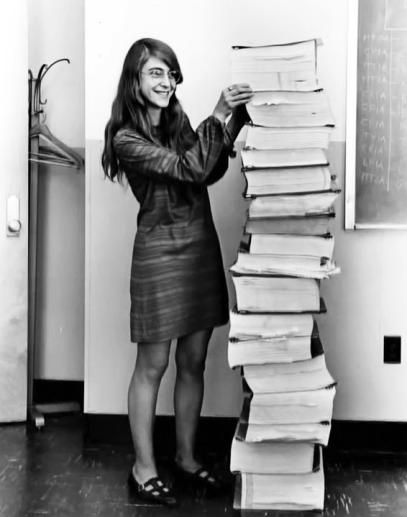 Margaret Hamilton standing next to listings of the actual Apollo Guidance Computer (AGC) source code.