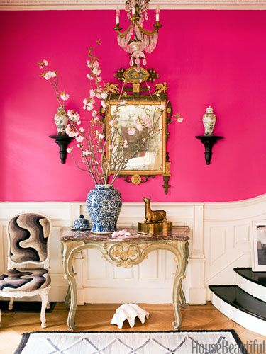 Exuberant Pink entry hall. But I like the paneling and the black lacquer stairs that fan out at the bottom