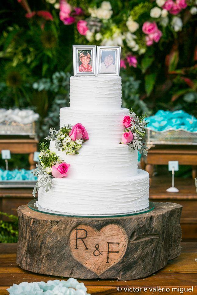 Bolo de casamento clássico todo em branco com rosas decorando as laterais. Como topo de bolo, fotos dos noivos ainda pequenos. Na base, as iniciais dos noivos em madeira.