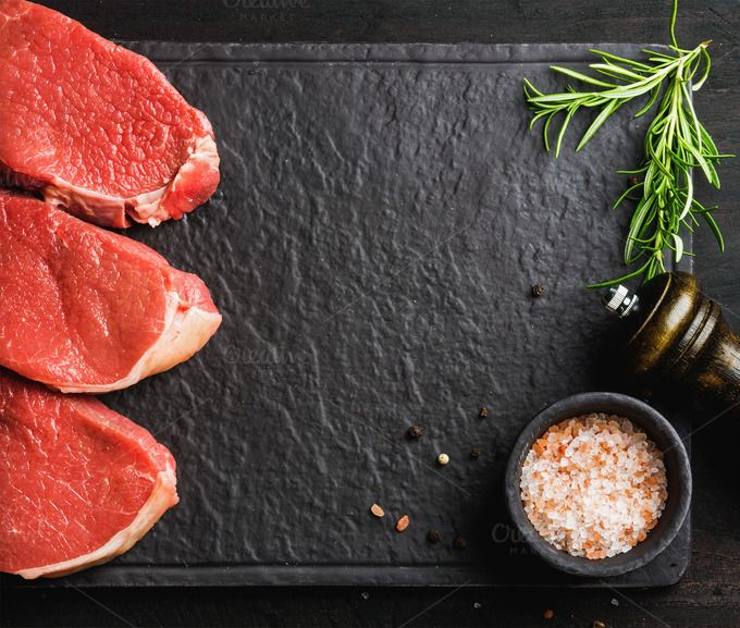 #Raw beef Eye Round steaks  Raw beef Eye Round steaks with spices and rosemary on black slate stone board over dark wooden background top view copy space horizontal composition