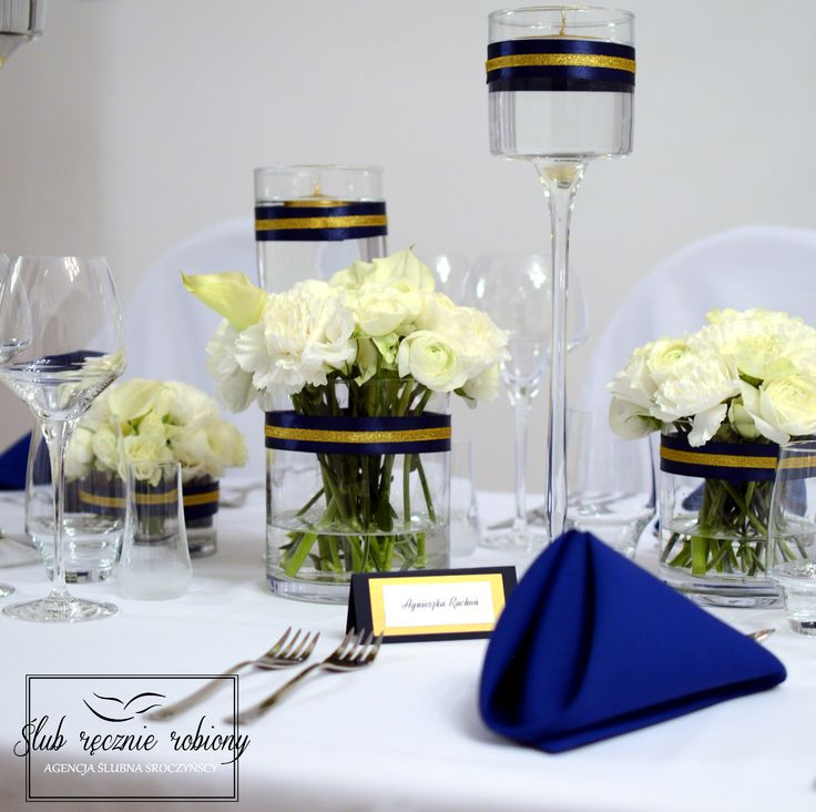"""White, gold and navy blue wedding table decorations all made by """"Slub Recznie Robiony"""" Wedding Planners. Gold candles in water, white, round centerpieces, gold and navy blue table numbers and name cards."""