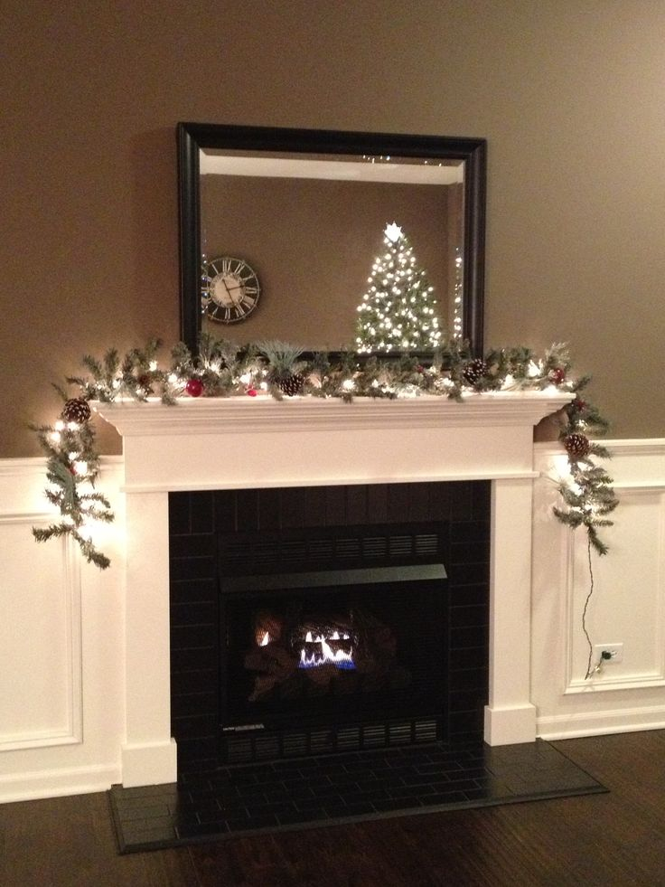 Black subway tile fireplace with white mantel and trim