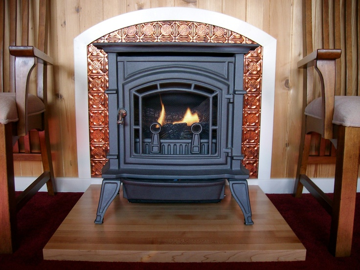 Wooden fireplace base fasade backsplash in moonstone copper finish used behind a gas fireplace - Fireplace finish ideas ...