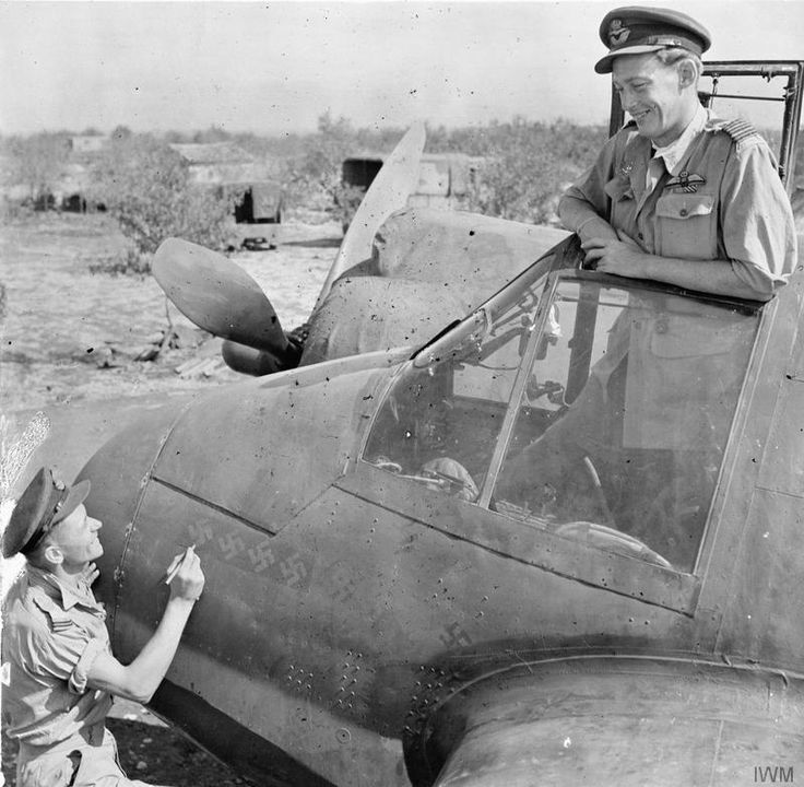 "Wing Commander C P ""Paddy"" Green, Commanding Officer of No. 600 Squadron RAF, watches from the cockpit of his Bristol Beaufighter Mark VIF at Cassibile, Sicily, as his radar operator, Flying Officer R J Gillies touches up the swastikas on the aircraft's nose, indicating the eight victories they had claimed while flying together as a night fighter crew. Seven of these victories were achieved during three consecutive nights in July over Sicily, four of them in a single sortie."