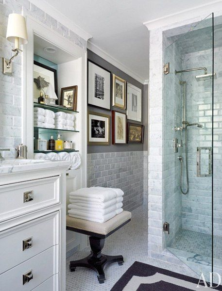 Grey and white bathroom with marble subway tile, nickel fixtures and gallery wall. Feels very cultured and despite all the white, masculine.