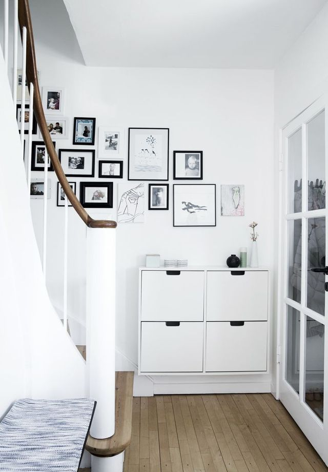 A spare nook washed in white with matching ceramic accents and bold black and white artwork.