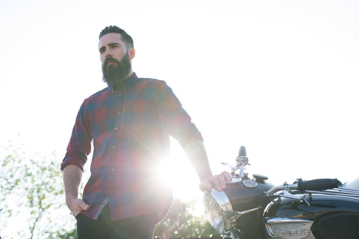 Bearded model in blue and red chequered shirt standing outside motorcycle workshops lit by bright, natural backlighting. #deuscustoms, #triumphmotorcycles #nortoncommando #nudiejeans #sevenwolves
