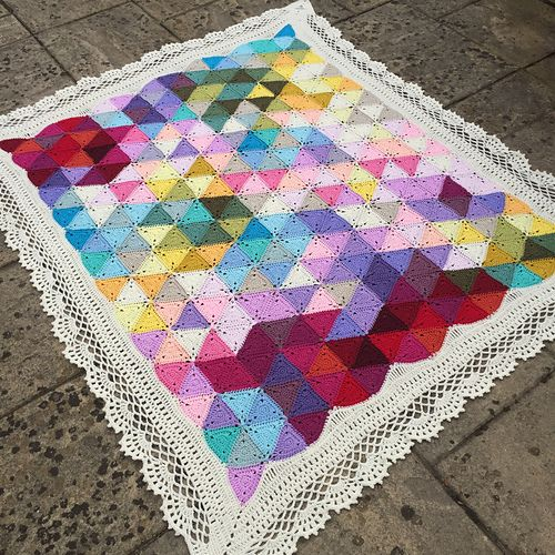 This is a detailed pattern, describing how to crochet a stunning triangle blanket with an elaborate lace edging, suitable for intermediate and advanced crocheters.