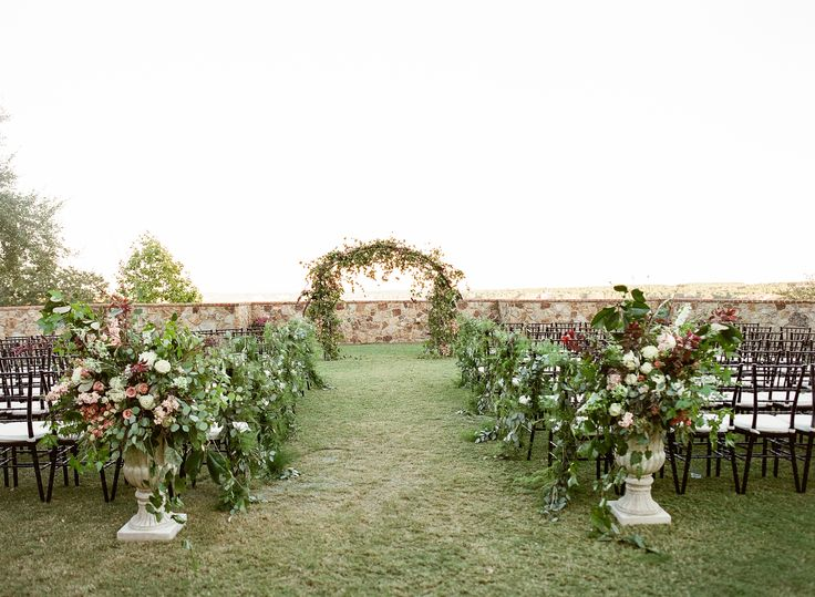 fall wedding at bella collina featured a large organic arch of greenery, berries, faded raintree blossoms & branches. loosely tied clusters of fern, vines and olive were fastened to the chairs on the aisle. two large, organic garden urns marked the entry to the ceremony site.