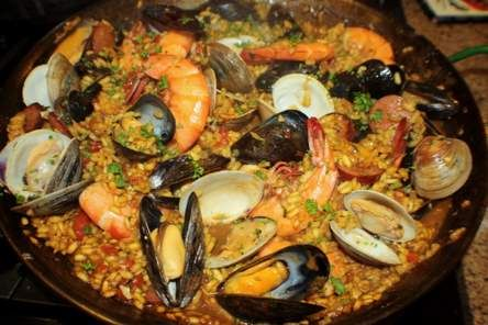 Paella is a popular Spanish dish commonly consisting of rice, chicken, beef, rabbitt, seafood, and vegetables. Most agree it originated in Valencia.