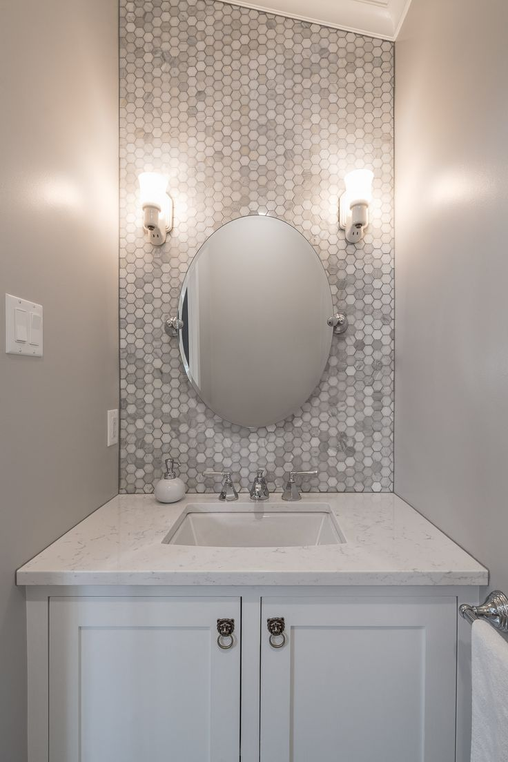 This tiny powder room got the star treatment with hexagonal Carrera marble tile to the ceiling!