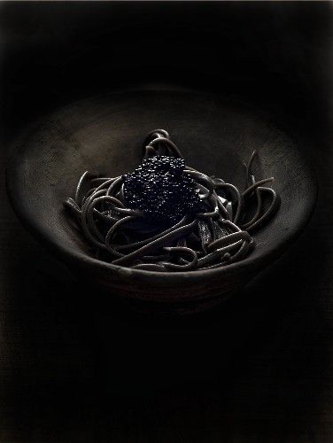 Squid ink pasta with caviar against black background