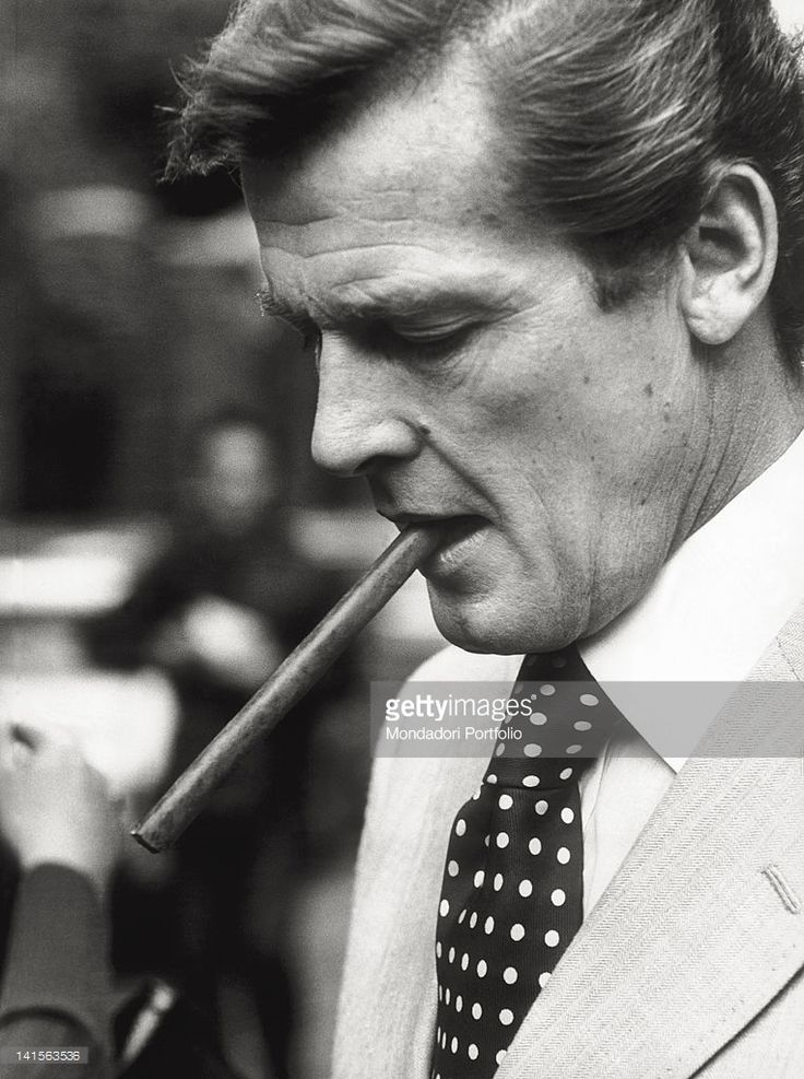 A close-up of the British actor Roger Moore smoking a cigar. Description from gettyimages.com. I searched for this on bing.com/images