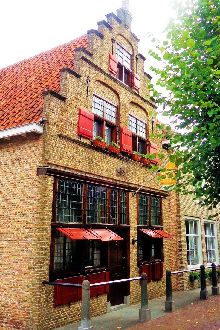 Het prachtige pand met de scheefstaande trapgevel met de fraaie rode luiken heet 'Inde Vrachwage' en is uit 1646.