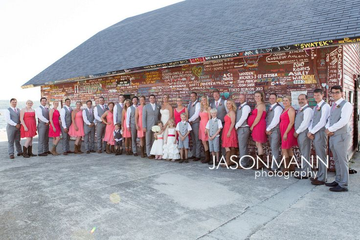 Large bridal party along Anderson Dock. Bridesmaids in pink dresses with cowboy boots and the groomsmen in gray suits. Door County wedding by http://www.JMannPhoto.com 920-246-8106