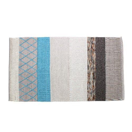Een wollen vloerkleed met verschillende gebreide patronen en kleuren.