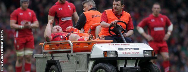 Wales prop Samson Lee is carried off the field with an injury to his left ankle after just 12 minutes