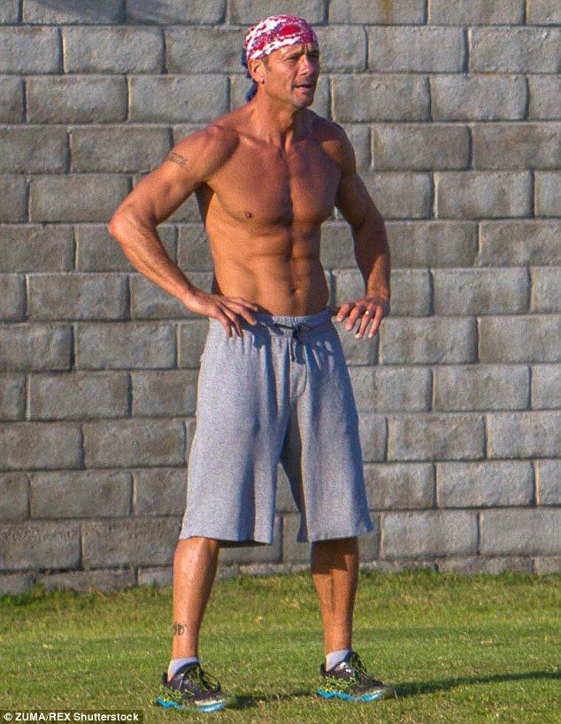 Buff: Tim McGraw shed his shirt for a gruelling workout in the park in San Diego on Wednesday
