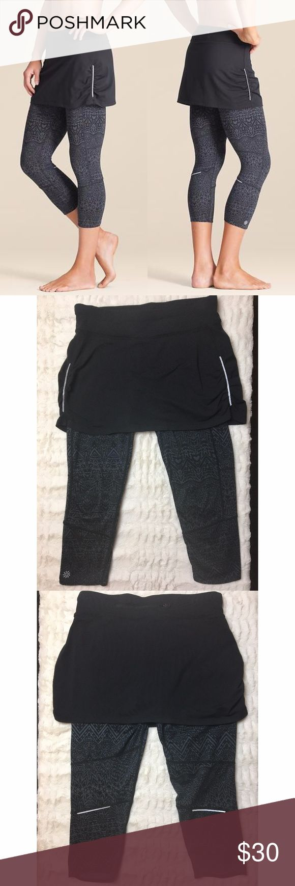Athleta | Maluku Contender 2-in-1 leggings/skirt Athleta Maluku Contender 2 in 1 leggings/skirt. Gray and black design. Ruching on sides. Performance fitted, mid-rise, tight leg. Reflective strips on sides and back of legs. Neverend drawstring that stays put. Zip pocket across back, and small pocket on front inner band. Moisture wicking and breathable. 50+ UPF protection. Super comfortable- smooth and stretchy! Lycra spandex provides a no-shine effect when stretched.  In very good condition…