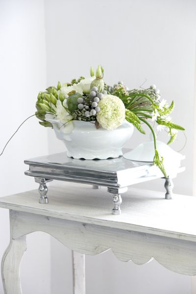 On a pedestal…  A rounded arrangement of grey Brunia, chincherinchees (Ornithogalum) and artichokes calls for a tad more than just a complementary vase – the silver pedestal gives it the spotlight it deserves.   wonder-flower, star-of-Bethlehem, chincherinchee; tjienk, tjienkerientjee, (Afr.) FOR MORE INSPIRATION: www.facebook.com/labolaweddings