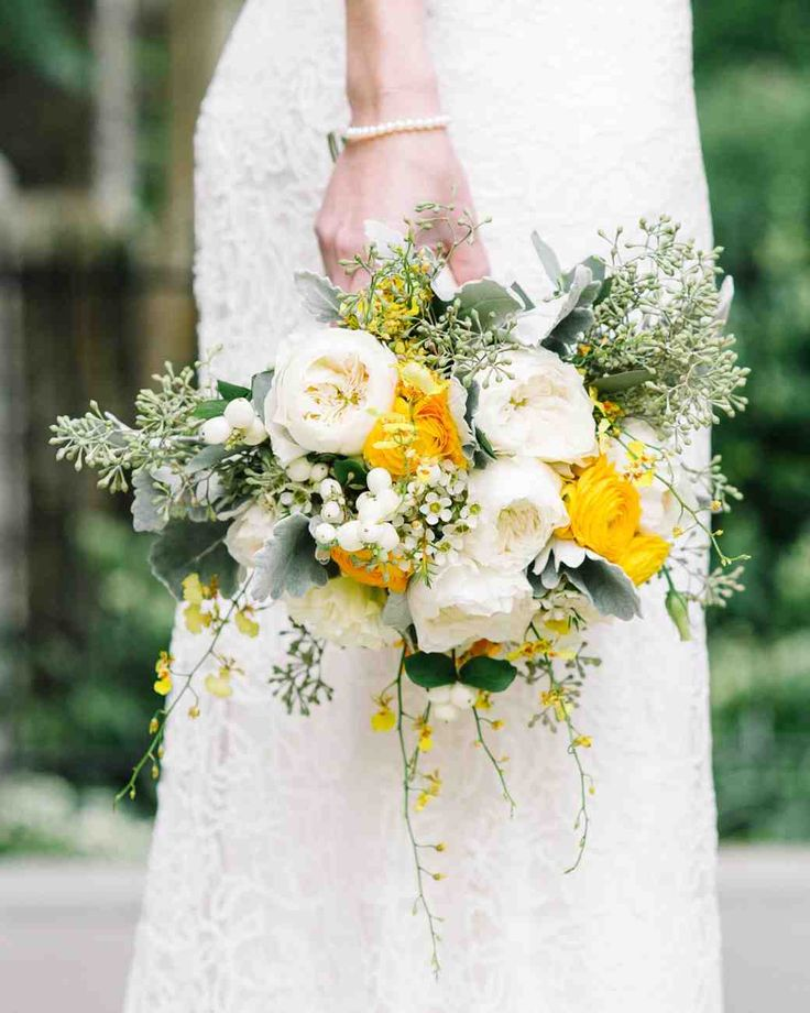 A Modern Yellow-and-White Wedding in Toronto | Martha Stewart Weddings - Amy carried a muted yet poppy mix of dusty miller, white snowberries, seeded eucalyptus, yellow oncidium and mokara orchids, yellow ranunculus, cream lisianthus, white garden roses, and white wax flowers. The bouquet was designed by Cool Green & Shady.