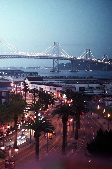San Francisco's Embarcadero waterfront area with piers and the SF-Oakland Bay Bridge in the background