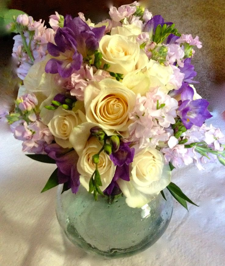 TJ's Gifts and Florals,  Ivory roses, purple freesia and lavender stock.