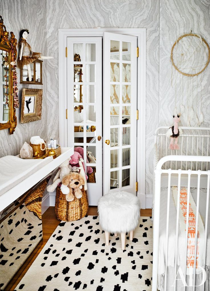 A pattern-packed nursery with black and white spotted rug, gray wallpaper, and gold changing station