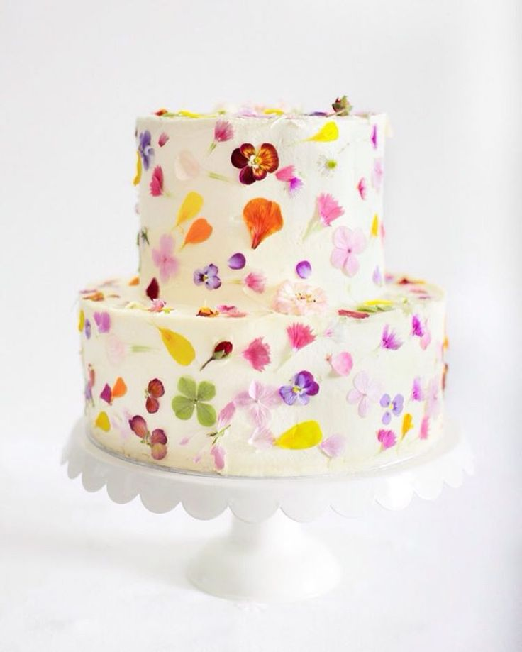 Dotted with a rainbow of edible flowers, this bright confection from @gillianbellcake has us dreaming of springtime.