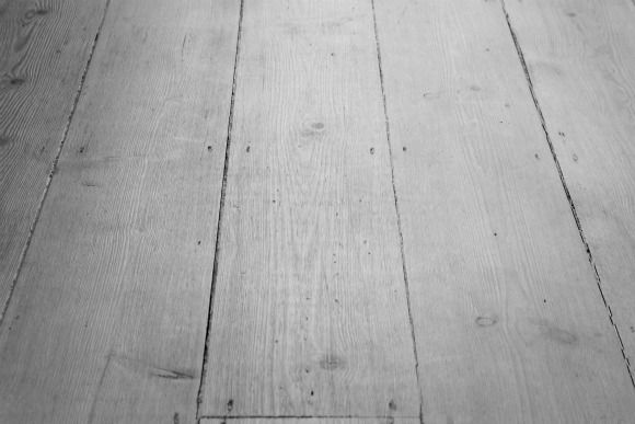 Old, mahogany stained floorboards brought to life by stripping back and applying an alkaline white wash