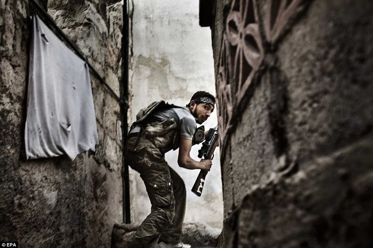 Second Prize, Spot News: This picture by Italian photographer Fabio Bucciarelli a Free Syrian Army fighter taking up a position during clashes against government forces in the Sulemain Halabi district in October 2012, Aleppo, Syria