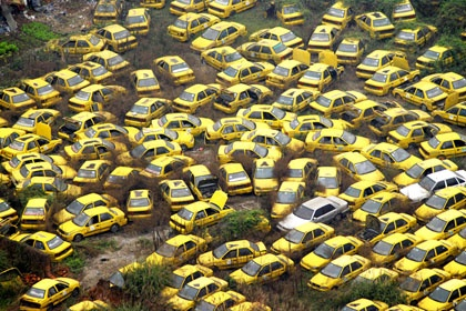 China/Chongqing:  Taxi Graveyard - Thousands of scrapped taxis are abandoned in a yard in the center of Chongqing, China. Traffic congestion and pollution have worsened dramatically in Chinese cities because the country's long-running economic expansion has allowed increasing numbers of consumers to make big-ticket purchases such as cars, which means many no longer have to rely on taxis or public transportation.