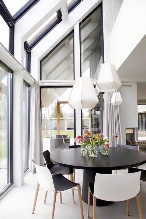 Beautiful black and white dining room with open windows looking over the backyard high ceilings and modern pendant lights femkeido interior design