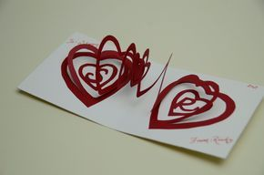 Here is the tutorial on making the Valentine's Day Spiral Heart Pop Up Card: Purchase the template for this design here: Valentine's Day Pop Up Card: Spiral Heart. Print out the template. Cut the 2 spiral heart templates out and tape them to some cardstock....