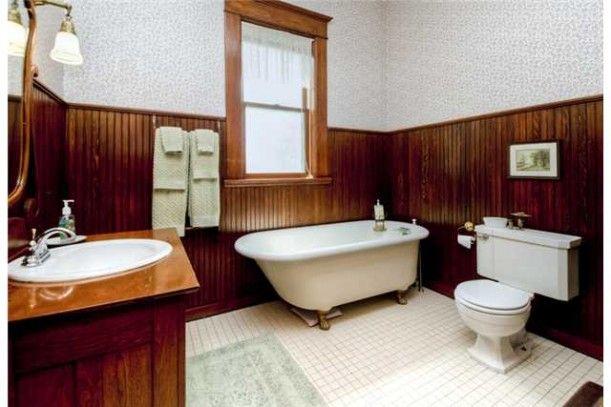 cuarto de baño con bañera con patas y wainscot