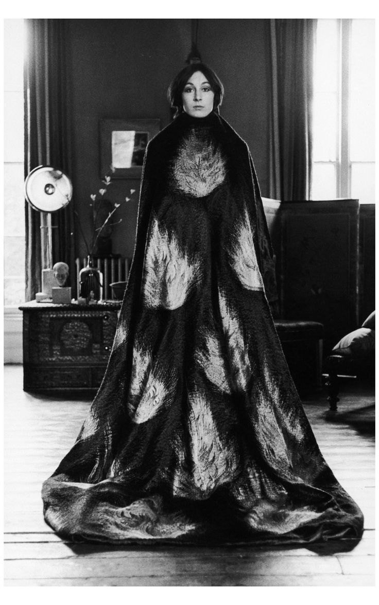 Anjelica Huston wearing a floor length cape decorated with a flame motif, early 1970s. (Photo by Terry O'Neill/Getty Images)